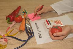 Nutritionist writing medical records and prescriptions with fresh fruits. Healthy, Diet concept Royalty Free Stock Photo