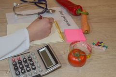 Nutritionist writing medical records and prescriptions with fresh fruits. Concept diet and weight loss Stock Photography