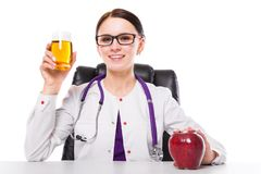 Nutritionniste féminin s'asseyant en son verre de représentation et de offre de lieu de travail de jus frais de pommes tenant la  photographie stock