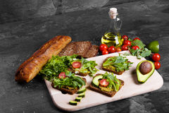 Vegetables near bread and jar of sauce on a stone background. Sandwiches with tomatoes, avocado and greens. Copy space. stock photo