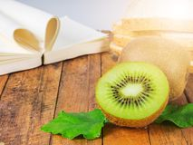 Nutritious breakfast. Kiwi fruit,brown rice bread and love notebook over wood background Stock Photography