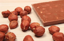 Nutritious chocolate and hazelnuts on wooden table Stock Images