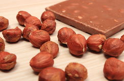 Nutritious chocolate and hazelnuts on wooden table Stock Photography