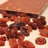 Nutritious chocolate with nuts and raisins on wooden table Royalty Free Stock Image
