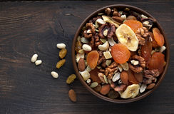 Nutritious dried fruits and nuts in bowl on wooden background. Top view, close-up Royalty Free Stock Photos
