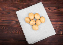 Nutritious, fresh, organic new potatoes in a gray fabric on the dark brown wooden table. Uncooked and tasty fresh vegetables. Stock Photo