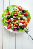Nutritious fresh salad with feta and olives. Nutritious fresh salad with feta, tomato, leafy greens and olives on a plate, overhead view on rustic white painted Royalty Free Stock Photo