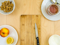 Nutritious healthy ingredients around board with knife, apple, cheese, walnuts and honey Stock Photography