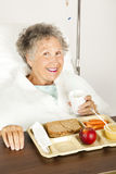 Nutritious Hospital Lunch. Senior woman in the hospital, eating her lunch from a tray Royalty Free Stock Photos