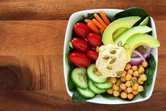 Nutritious lunch bowl with avocado, hummus and vegetables on wood Stock Images