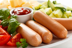 Nutritious lunch -sausages and vegetable salad Royalty Free Stock Images
