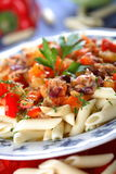 Nutritious meals. Macaroni with tuna fish and tomatoes on the plate Stock Images