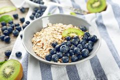 Nutritious oatmeal with kiwi and blueberry. On table Royalty Free Stock Photo