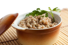 Nutritious porridge in the ceramic pot. Close up. Isolated on white Stock Image