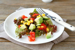 Nutritious salad with avocado, tomatoes and corn on a plate Stock Photo