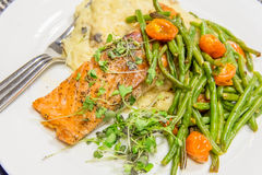 Nutritious salmon dinner with green beans and tomatoes. Nutritious salmon dinner with green beans, mashed potatoes and roasted tomatoes Royalty Free Stock Photos