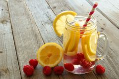 Nutritious water with lemon and raspberries on wood background Stock Photo