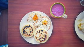 A nutritive breakfast. Pair of arepas and eggs with a berries smoothie for breakfast royalty free stock images