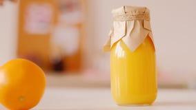 Nutrizione di rotolamento arancio del frullato della bottiglia di vetro video d archivio