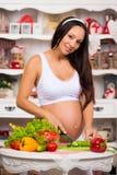 Nutrizione e gravidanza sane La giovane donna incinta sorridente taglia le verdure su insalata Fotografie Stock Libere da Diritti