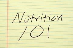 Nutrizione 101 su un blocco note giallo Fotografia Stock