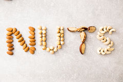 NUTS λέξης που συλλαβίζουν με τα διάφορα καρύδια στο υπόβαθρο stona Assorte Στοκ φωτογραφία με δικαίωμα ελεύθερης χρήσης