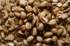 Nuts. Close up of pistachios and cashews on chopping board in kirchen Royalty Free Stock Images