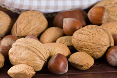 Nuts. Little basket with nuts, over wooden table Royalty Free Stock Image