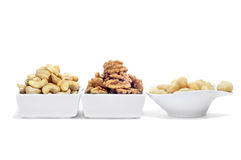 Nuts. Some bowls with different nuts, as cashews, walnuts and Macadamia nuts on a white background stock photo