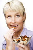 Nuts. Young beautiful blond woman eating nuts close up Stock Image