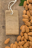 Nuts almond and tag price on wood Stock Photo