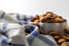 Nuts, almond, tasty and healthy food with lots of vitamins. Almond nuts placed in white cup on a kitchen towel. Closeup view. Selective focus stock photos
