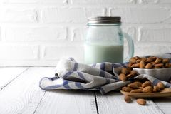 Nuts, almond, tasty and healthy food with lots of vitamins. Almond nutsin bowl near glass jar with almond milk. On white wooden table near white bricks wall stock photo