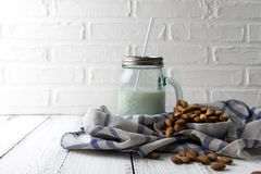 Nuts, almond, tasty and healthy food with lots of vitamins. Almond nutsin bowl near glass jar with almond milk on white wooden royalty free stock photo