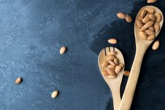 Nuts, almond, tasty and healthy food with lots of vitamins. Almond nuts placed in and near wooden spoons on dark background.  stock photo