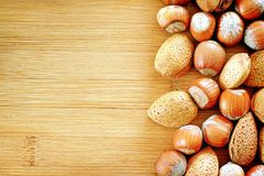 Nuts and almonds. On wooden plate with a lot of space for text Royalty Free Stock Images