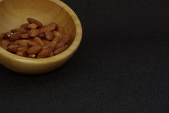 Nuts almonds in a bamboo bowl, on a dark background, healthy diet for weight loss, copyspace Stock Images
