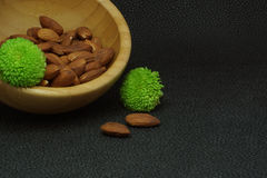 Nuts almonds in a bamboo bowl, on a dark background, healthy diet for weight loss, green flowers Stock Photos