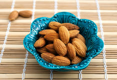 Nuts of almonds in a beautiful blue bowl Stock Photography
