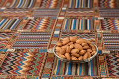 Nuts almonds on a carpet. Nuts almonds on a traditional Arabian carpet Stock Photo