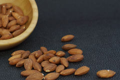 Nuts almonds poured out of a bamboo bowl, on a dark background, healthy diet for weight loss Stock Photo