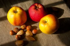 Nuts and apples in the background. hazelnuts and almonds.  Royalty Free Stock Image
