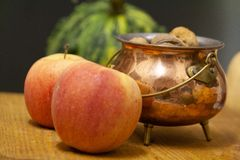 Nuts, apples and pumpkins on wooden board stock photo