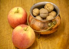 Nuts, apples and seeds on wooden board royalty free stock photo