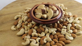 Nuts background. Almond, cashew and brazilian nuts on wooden table stock footage