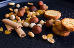 Nuts, baguettes, sticks, rasin on a black baking pan Royalty Free Stock Images