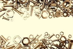 Nuts and bolts. Chrome nuts and bolts closeup on plain background Stock Image