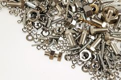 Nuts and bolts. Chrome nuts and bolts closeup on plain background Royalty Free Stock Photo