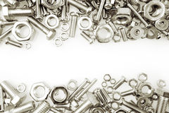 Nuts and bolts. Chrome nuts and bolts closeup on plain background Royalty Free Stock Images