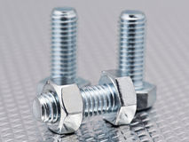 Nuts and bolts on metal background Royalty Free Stock Photo